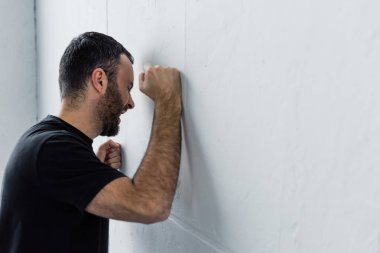 adult depressed man screaming while standing by white wall at home