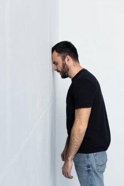 frustrated bearded man in black t-shirt standing near white wall with closed eyes