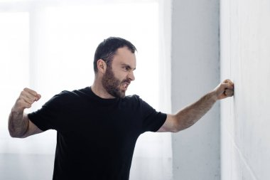 angry bearded man in black t-shirt kicking white wall with hand