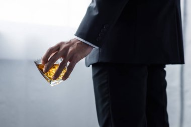 partial view of man in black suit holding glass of whiskey