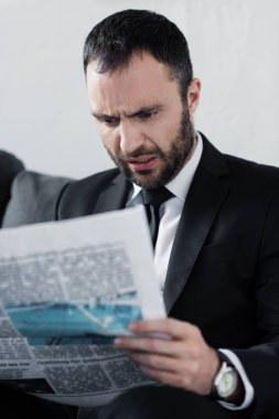 Selective focus of shocked bearded businessman reading newspaper stock vector