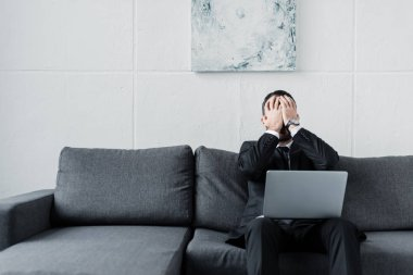 upset businessman holding hands on face while sitting on grey sofa with laptop