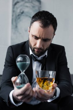 selective focus of depressed businessman holding glass of whiskey and hourglass