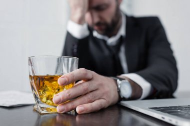 selective focus of depressed businessman holding glass of whiskey