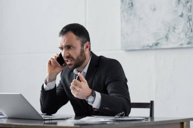 angry businessman yelling while sitting at workplace and talking on smartphone