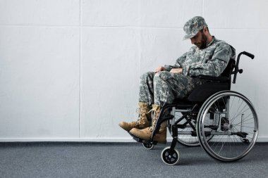 Depressed disabled military man in uniform sitting in wheelchair with bowed head stock vector