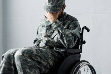 Depressed disabled military man in uniform sitting in wheelchair and covering face with hand stock vector
