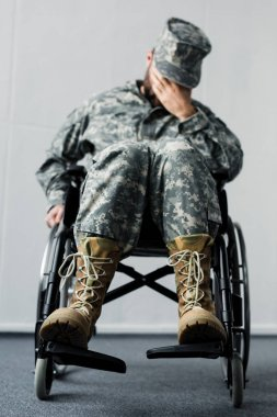 Selective focus of disabled military man in uniform sitting in wheelchair and covering face with hand stock vector