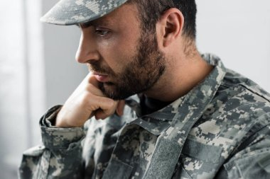 Pensive bearded military man in uniform holding hand near face stock vector