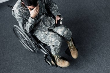Overhead view of disabled military man in uniform sitting with flask in wheelchair and covering face with hand stock vector