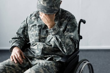Depressed disabled man in military uniform sitting in wheelchair and holding hand on face stock vector
