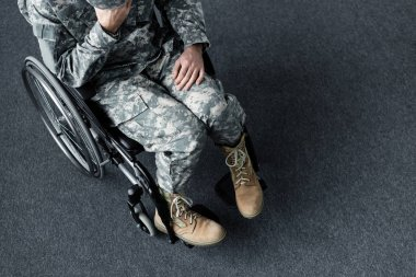 Overhead view of depressed disabled man in military uniform sitting in wheelchair stock vector