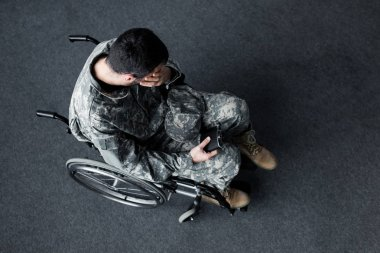 Overhead view of disabled man in military uniform sitting in wheelchair and covering face with hand stock vector