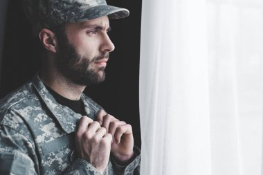 Thoughtful bearded man in military uniform standing by window and looking away stock vector