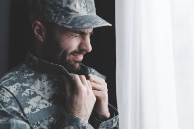 Depressed bearded man in military uniform crying while standing by window stock vector