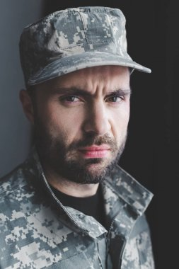 Serious bearded man in military uniform and cap looking at camera stock vector