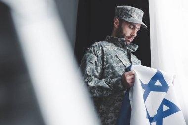 Selective focus of thoughtful military man in uniform holding israel national flag while standing by window stock vector