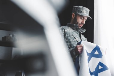 Selective focus of pensive bearded man in military uniform holding israel national flag while standing by window stock vector