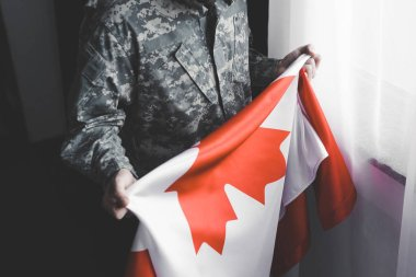 Partial view of man in military uniform holding canada national flag while standing by window stock vector