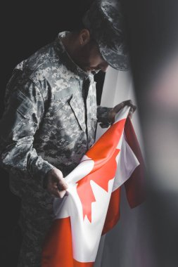 Selective focus of depressed man in military uniform holding canada national flag stock vector
