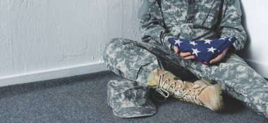 Cropped view of man in military uniform sitting on floor in corner and holding usa national flag stock vector
