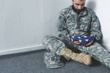 Sad bearded man in military uniform sitting on floor in corner and holding usa national flag stock vector