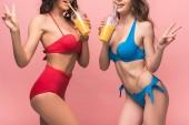 oříznutý pohled na dvě dívky v bikinách popíjí pomerančovou šťávu a vykazují mírové znaky izolované na růžovém