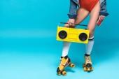 oříznutý pohled na ženu v plavkách a kolečkových brusle držící na modrém radiomagnetofon a kazetu s kazetou