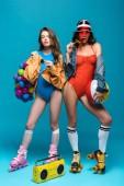 Fotografia full length view of two stylish girls in roller skates eating watermelon lollipop on blue