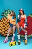pohled na dvě stylové dívky v kolečkových brusle s plážovým míčkem a s meloun na modré lízátka