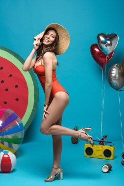 full length view of woman in swimsuit and straw hat standing on one leg on blue