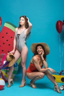 full length view of two happy girls in swimsuits and straw hats on blue