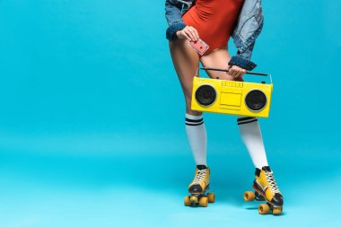 cropped view of woman in swimsuit and roller skates holding boombox and cassette tape on blue