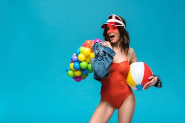 excited girl in swimsuit and roller skates holding beach ball and sting bag with colorful balls isolated on blue