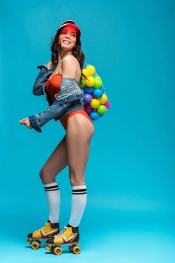 full length view of smiling girl in swimsuit and roller skates holding string bag with colorful balls on blue