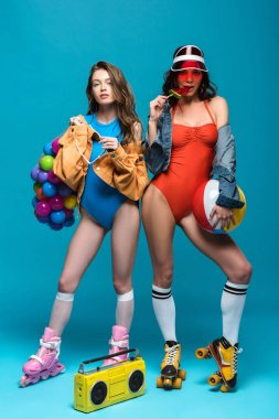 full length view of two stylish girls in roller skates eating watermelon lollipop on blue