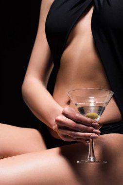 cropped view of sexy woman holding glass of martini with olive isolated on black