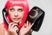 krásná nudná žena v růžové paruce přidržící Retro telefon, izolovaná na šedé