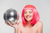 attractive happy girl in pink wig holding disco ball, isolated on grey