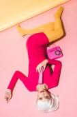 pohled na stylovou atraktivní ženu v bílé paruce s retro telefonem na růžovém