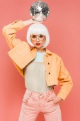 beautiful girl in white wig posing with disco ball, isolated on pink
