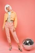 gyönyörű lány, fehér paróka jelentő közelében disco labdát rózsaszín