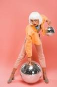 divatos nő fehér paróka pózol disco labdák rózsaszín