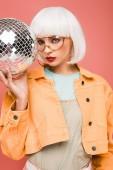 stílusos lány fehér paróka és napszemüveg pózol disco labdát, izolált rózsaszín