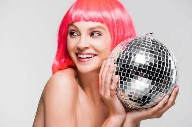 attractive girl in pink wig holding disco ball, isolated on grey