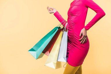 Cropped view of stylish woman with shopping bags, isolated on yellow stock vector