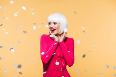 beautiful surprised woman in red dress and white wig posing with holiday confetti, isolated on yellow