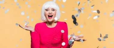 excited surprised girl in red dress and white wig posing with holiday confetti, isolated on yellow
