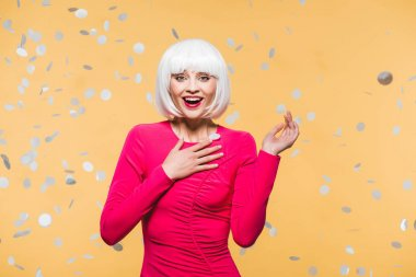 surprised girl in red dress and white wig posing with holiday confetti, isolated on yellow