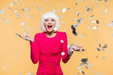 excited girl in red dress and white wig posing with holiday confetti, isolated on yellow